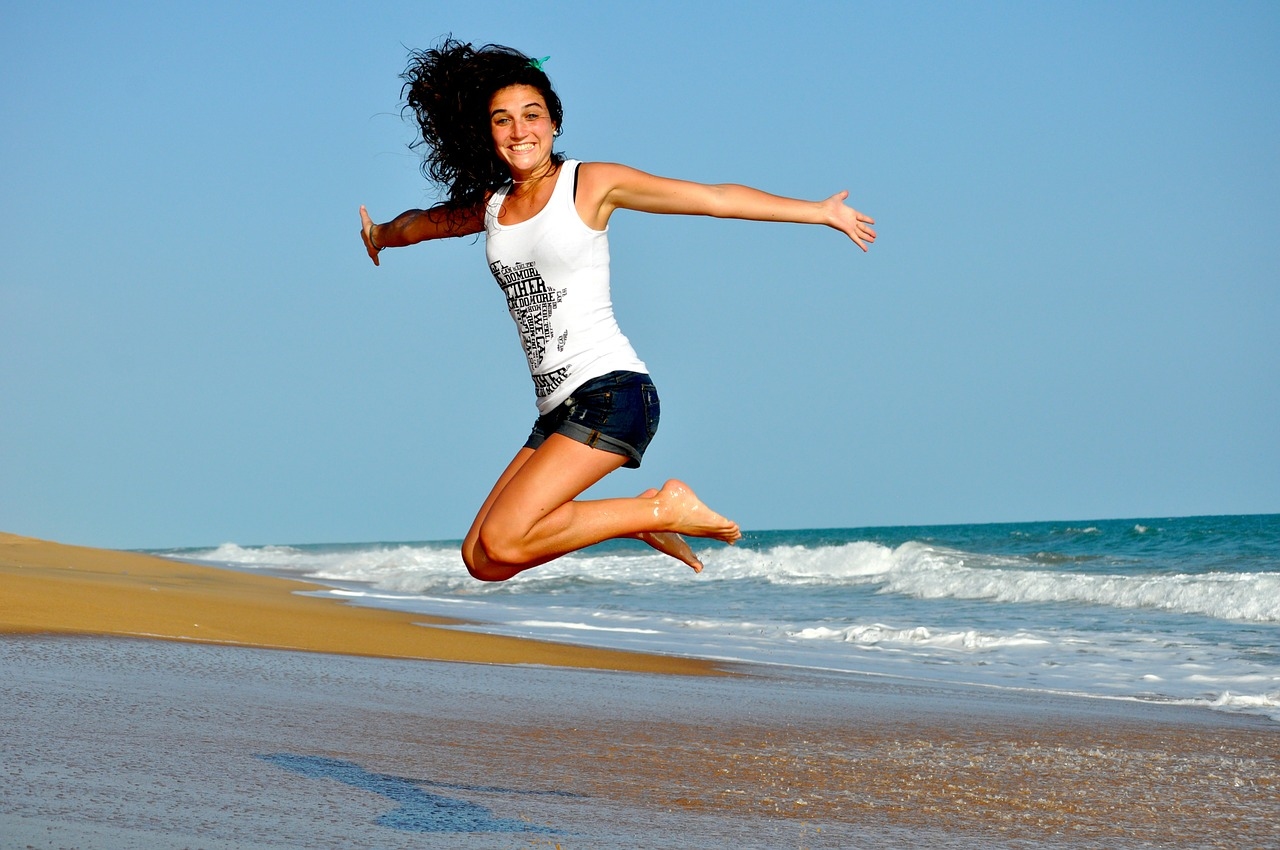 jumping woman in front of sea